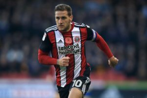 Billy Sharp scored a hat-trick as Sheffield United beat Wigan 4-2 to move two points clear at the top of the Sky Bet Championship.