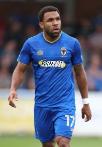 Winger Andy Barcham will miss AFC Wimbledon's League One clash with Luton on Saturday.