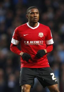 Carlisle midfielder Kelvin Etuhu has triggered an extension clause in his contract that will keep him at the club until the end of next season.