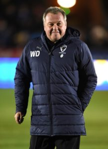 Wally Downes hailed his team's determination as AFC Wimbledon, League One's bottom side, collected a point from a goalless draw at Shrewsbury.