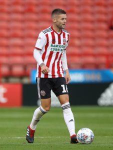 Ten-man Sheffield United recorded their eighth straight home league win, beating Brentford 2-0 to maintain their drive for automatic promotion.