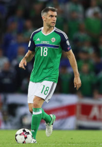 Former Northern Ireland star Aaron Hughes has paid tribute to coach Michael O'Neill after he confirmed his retirement from football.