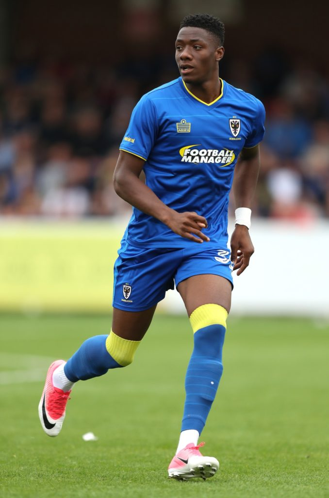 AFC Wimbledon manager Wally Downes has urged Paul Kalambayi to take the next step in his development after the defender signed a new contract.