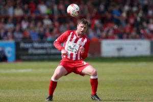 Accrington centre-back Mark Hughes has signed an improved contract to remain at the club until at least 2020.