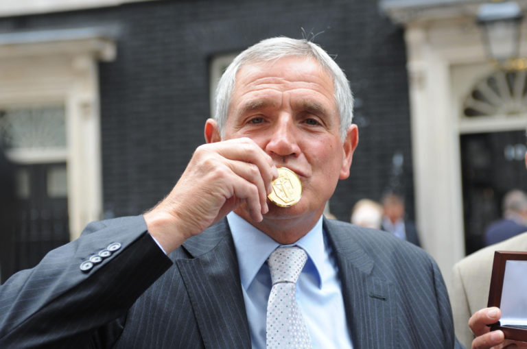 Norman Hunter kisses his 1966 World Cup winner's medal, presented to him by Prime Minister Gordon Brown in 2009