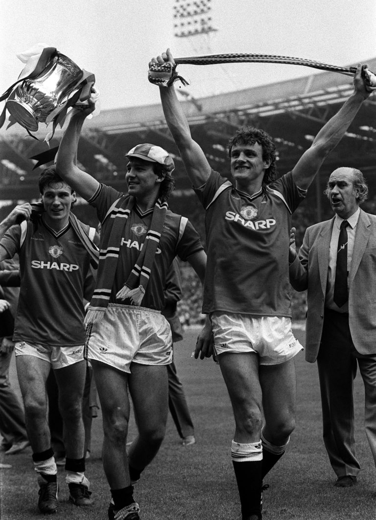 Manchester United captain Bryan Robson shows off the FA Cup after beating Everton in 1985