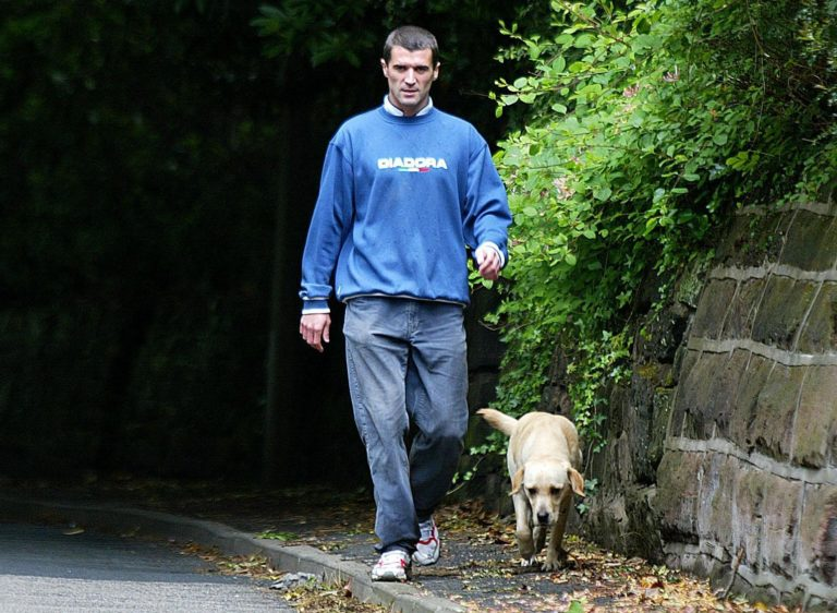 Roy Keane walks his dog outside his home in Hale Barnes after being sent home from the World Cup