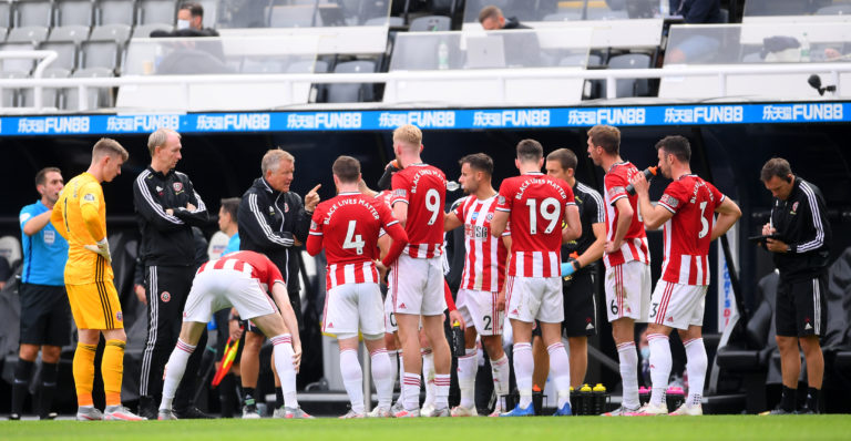 Chris Wilder talks to his players during a drinks break at St James' Park