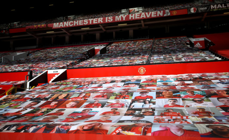 Fan pictures on banners covering the seats in the stands at Old Trafford