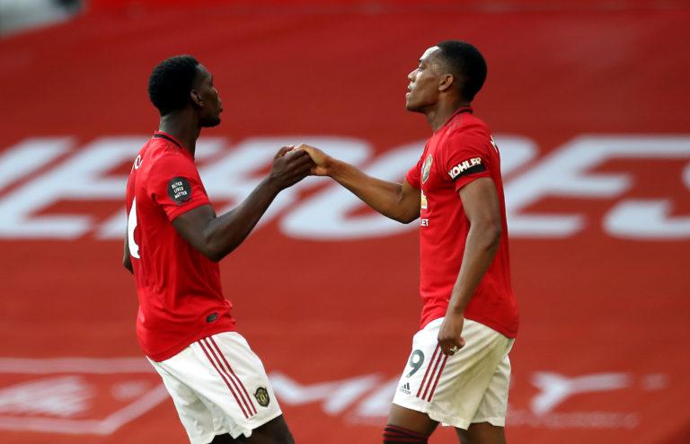 Martial celebrates scoring his third goal with Paul Pogba, left
