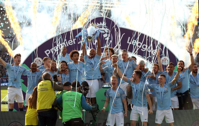 Manchester City's Vincent Kompany (centre) lifts the Premier League trophy at Brighton last year