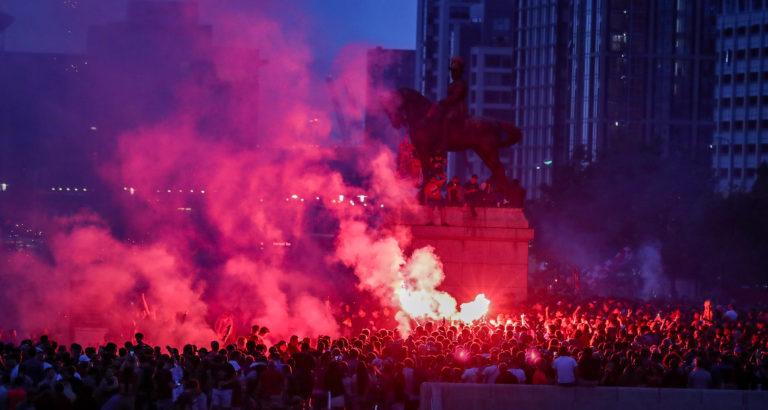 Liverpool fans let off flares outside the Liver Building