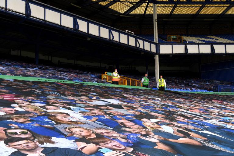 A banner picture of fans covers the seats in the stands before the Merseyside derby on June 21