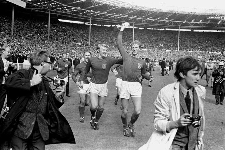Charlton holds the Jules Rimet trophy aloft