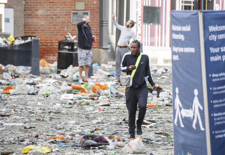 People walk past litter in the centre of Leeds after celebrations by fans whose football club won the Championship title and a return to the Premier League