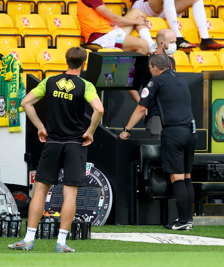 Referee Kevin Friend checks the VAR monitor in a match between Norwich and Burnley